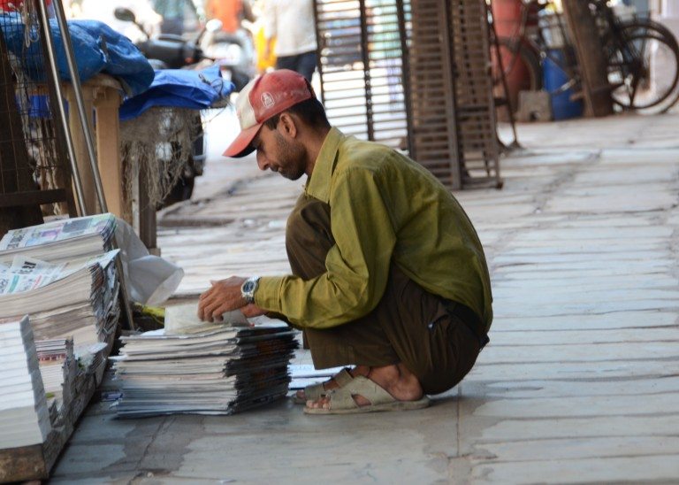 The newspaper man bundling his left over newspapers