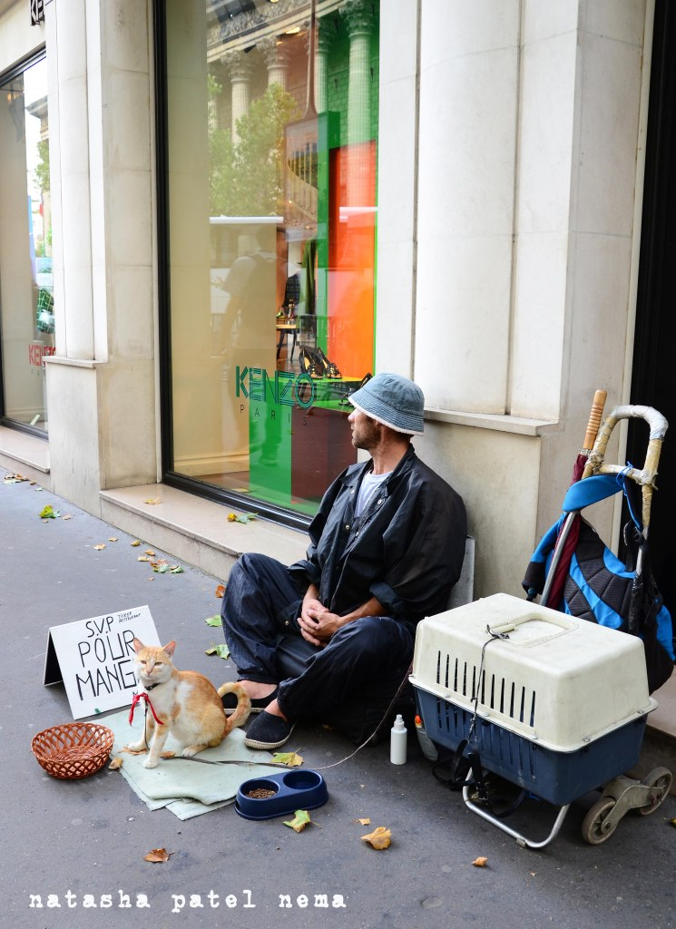A bagger siting out a posh shop with his cat and his belongings