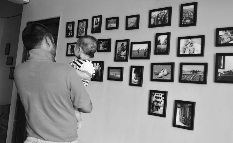 Father and son take a last look at our wall with photographs before packing it up
