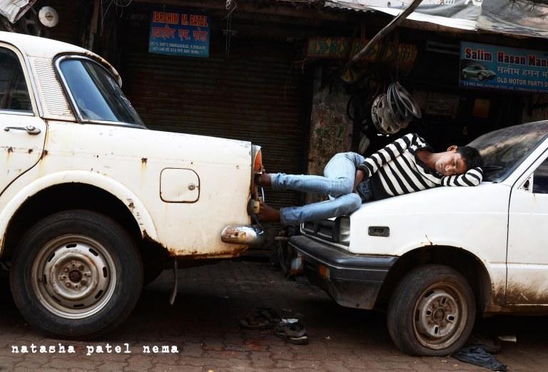 A boy sleeping outside a car garage at Mumbia chor bazzar