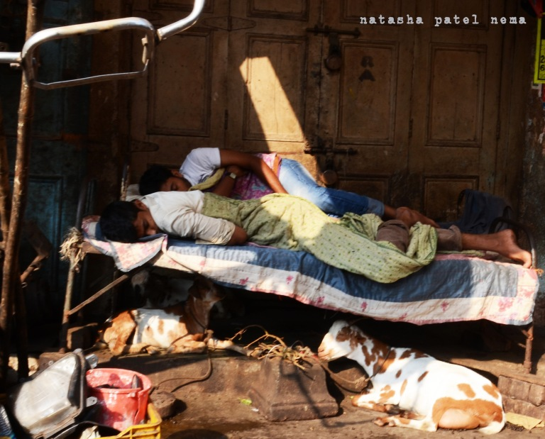 men sleeping outside a shop early morning with thier goats tied under thier bed at Mumbai Chor bazzar