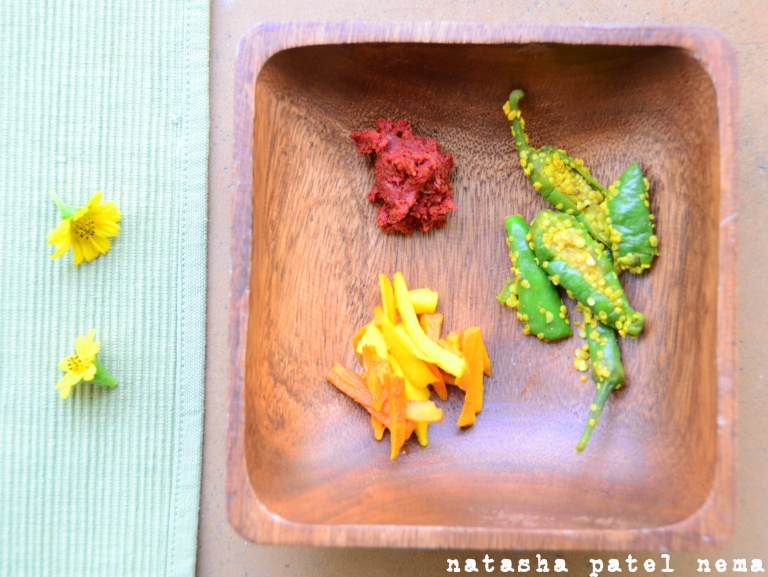 Accompaniments with dal batti, spicy garlic chutney, pickled chiles and pickled turmeric